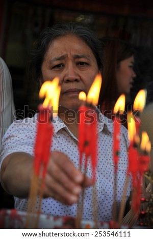 BANGKOK - JAN 30: A temple goer places candles while making merit at a Chinatown Taoist-Buddhist shrine during festivities ushering in the Chinese New Year on Jan 30, 2014 in Bangkok, Thailand. - stock photo