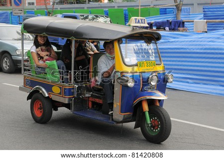BANGKOK - JAN 20: A three wheeled tuk tuk taxi on a street in the Thai capital on January 20, 2011 in Bangkok, Thailand. Tuk tuks are commonly used in transporting people and goods around the capital. - stock photo
