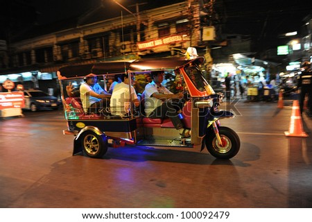 BANGKOK - JAN 15: A three wheeled tuk tuk taxi transports passengers along road on Jan 15, 2012 in Bangkok, Thailand. Tuk tuks can be hired from as little as $1 or B30 a fare for short trips. - stock photo