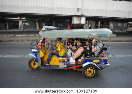 BANGKOK - JAN 14: A tuk tuk taxi transports passengers along a road in the city centre on Aug 12, 2013 in Bangkok, Thailand. Tuk tuks can be hired from as little as $1 or B30 a fare for shop trips. - stock photo