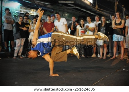 BANGKOK - JAN 4: An unidentified b-boy breakdances at an informal street dance meet on Jan 4, 2011 in Bangkok, Thailand. Breakdancing is a popular activity of youth in the Thai capital. - stock photo