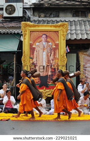 BANGKOK - JAN 25: Buddhist monks walk past a large portrait of the Thai King while making a pilgrimage on Jan 25, 2013 in Bangkok, Thailand. 1,128 monks are taking part in the pilgrimage. - stock photo