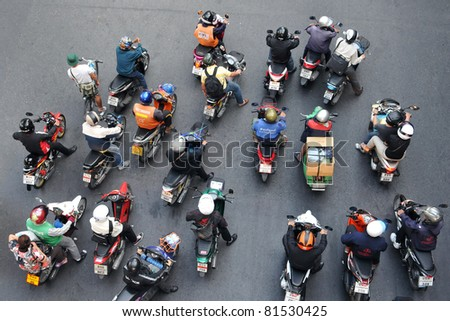 BANGKOK - JAN 13: Motorcyclists wait at a junction  during rush hour on Jan 13, 2011 in Bangkok, Thailand. Motorcycles are often the transport of choice for Bangkok's heavily congested roads. - stock photo