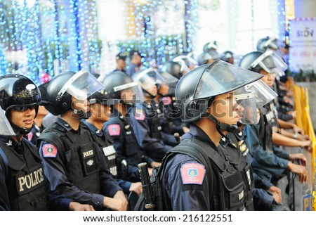 BANGKOK - JAN 9: Riot police block an entrance to Sukumvit Road during a 30,000 strong anti government Red Shirt protest in the city centre of the Thai capital on Jan 9, 2011 in Bangkok, Thailand. - stock photo