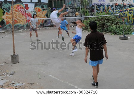 BANGKOK - JAN 20: Takraw players compete in a street match on derelict land Jan 20, 2011 in Bangkok, Thailand. Takraw also known as Kick Volleyball is one of the national sports of Thailand. - stock photo
