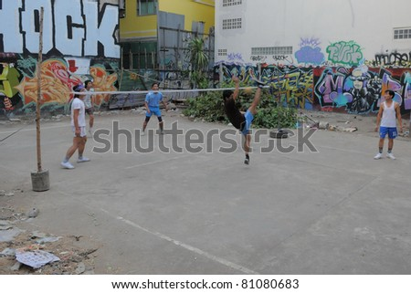 BANGKOK - JAN 20: Takraw players compete in a street match on derelict land Jan 20, 2011 in Bangkok, Thailand. Takraw or Kick Volleyball is one of the national sports of Thailand. - stock photo