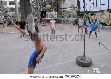 BANGKOK - JAN 20: Takraw players compete in a street match on derelict land on Jan 20, 2011 in Bangkok, Thailand. Takraw or sometimes Kick Volleyball is one of the national sports of Thailand. - stock photo