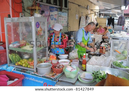 BANGKOK - JAN 20: Unidentified street vendors cook at a roadside restaurant Jan 20, 2011 in Bangkok, Thailand. There are more than 16,000 registered street vendors in Bangkok. - stock photo
