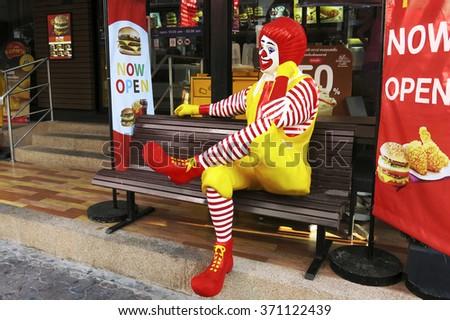 BANGKOK - JANUARY 02, 2016:Ronald McDonald character sitting on bench at McDonald Restaurant in Bangkok,Thailand. McDonald's Corporation is the world's largest burger fastfood restaurants. - stock photo