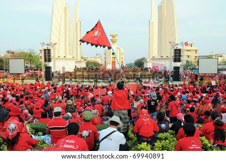 BANGKOK - JANUARY 23: Thousands of anti-government red-shirt protesters converge at Democracy Monument on January 23, 2011 in Bangkok, Thailand. The red-shirts are calling for political change. - stock photo