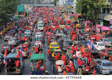 BANGKOK - JANUARY 23: Thousands of anti- government Red Shirt protesters leave Ratchaprasong Junction en route to a rally site at Democracy Monument on January 23, 2011 in Bangkok, Thailand. - stock photo