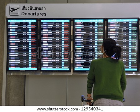 BANGKOK - JULY 6: A traveller views a departures board at Suvarnabhumi International Airport on July 6, 2012 in Bangkok, Thailand. The airport handles 45 million passengers annually. - stock photo