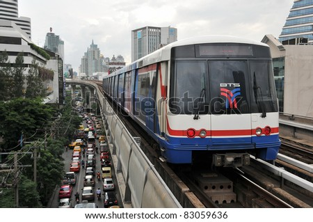 BANGKOK - JULY 20: BTS Skytrain on elevated rails above Sukhumvit Road on July 20, 2011 in Bangkok, Thailand. Each train of the mass transport rail network can carry over 1,000 passengers. - stock photo