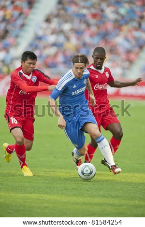 BANGKOK - JULY 24 : F.Torres (B) in action during Coke Super Cup : Chelsea  Asia Tour 2011 (Thailand),  between Chelsea vs Thail  All-Star on July 24, 2011 in Rajamangla Stadium,Bangkok, Thailand. - stock photo