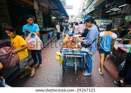 BANGKOK - JULY 29 : Street market sellers busy attend their customers at one of the China town streets July 29, 2007 in Bangkok, Thailand. China town is one of the biggest districts of Bangkok. - stock photo