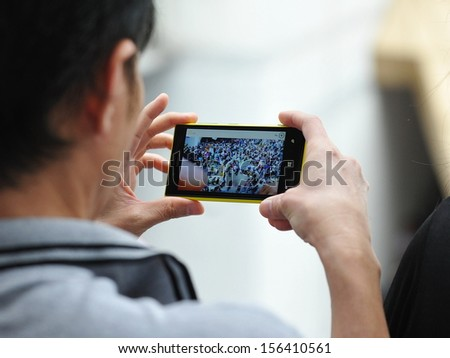 BANGKOK - JUN 30: A passerby uses a smartphone to capture an anti-government rally on Jun 30, 2013 in Bangkok, Thailand. The protesters known as V for Thailand call for the government to be removed. - stock photo