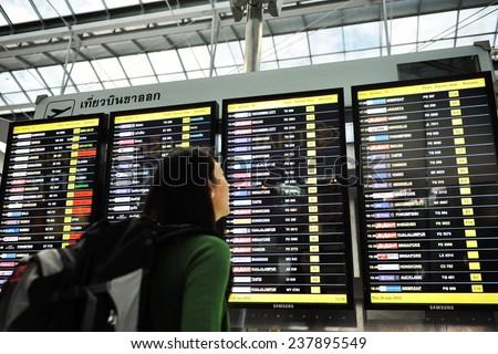 BANGKOK - JUN 28: An air traveler views a flight notice board in the departures terminal of Suvarnabhumi Airport on Jun 28, 2012 in Bangkok, Thailand. The airport handles 45 million passengers a year. - stock photo