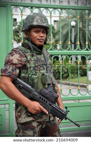 BANGKOK - JUN 26: An unidentified armed Thai soldiers stands guard outside a military installation as anti election protesters hold a rally nearby on Jun 26, 2011 in Bangkok, Thailand.  - stock photo
