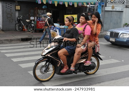 BANGKOK - JUN 5: Unidentified people ride a motorbike on a city street on Jun 5, 2013 in Bangkok, Thailand. Road safety laws across Thailand are often unenforced and poorly observed. - stock photo