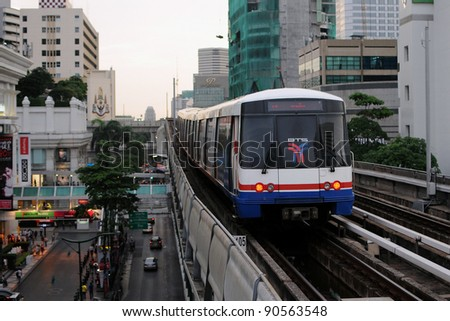 BANGKOK - JUNE 21: A BTS Skytrain on elevated rails above Sukhumvit Road on June 21, 2011 in Bangkok, Thailand. Each train of the mass transport rail network can carry over 1,000 passengers. - stock photo