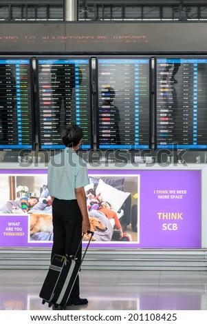 BANGKOK - JUNE 21 : A traveler views a departures board at Suvanaphumi Airport, Bangkok on JUNE 21, 2014,Suvarnabhumi airport is world's 4th largest single-building airport terminal. - stock photo