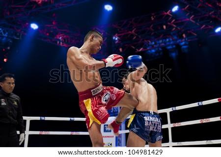 "BANGKOK - JUNE 9: Muay Thai Super Lightweight World Championship - Jomtong Chuwattana (TH) kicking Yetkin Ozkul (Turkey) in his liver at ""BATTLE FOR THE BELTS"" on June 9, 2012 in Bangkok, Thailand - stock photo"