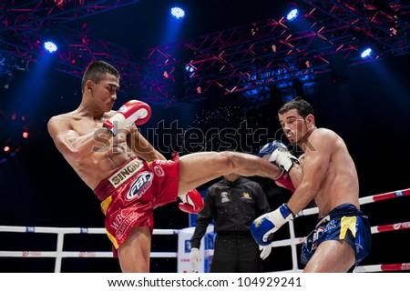 "BANGKOK - JUNE 9: Muay Thai Super Lightweight World Championship - Jomtong Chuwattana (Thailand) kicking Yetkin Ozkul (Turkey) at ""BATTLE FOR THE BELTS"" event on June 9, 2012 in Bangkok, Thailand - stock photo"