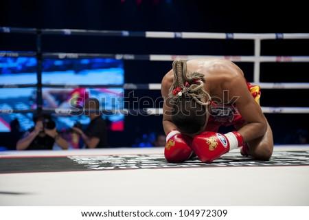 "BANGKOK - JUNE 9: Muay Thai Super Lightweight World Championship - Jomtong Chuwattana (Thailand) praying ritual before the fight at ""BATTLE FOR THE BELTS"" event on June 9, 2012 in Bangkok, Thailand - stock photo"