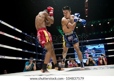 "BANGKOK - JUNE 9: Muay Thai Super Welterweight World Championship fight - Kem Sitsongpeenong (THA) hitting Alejandro Asumu Osa (ES) at ""BATTLE FOR THE BELTS"" event on June 9, 2012 in Bangkok, Thailand - stock photo"