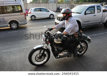 BANGKOK - MAR 26: A motorcyclists rides a Triumph Bonneville bike on a city street on Mar 26, 2013 in Bangkok, Thailand. Founded in 1902 Triumph is now Britain's largest motorbike manufacturer. - stock photo