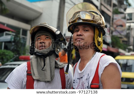 BANGKOK - MAR 5: Firefighters look on at blaze at Fico Building on Asoke Road in the city centre on Mar 5, 2012 in Bangkok, Thailand. The BMA has launched an investigation in the cause of the blaze. - stock photo