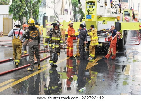 BANGKOK - MAR 3: Firefighters tackle a blaze at Fico Building in the city centre on Mar 3, 2012 in Bangkok, Thailand. The city government has launched an investigation in the cause of the blaze. - stock photo