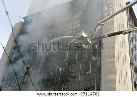 BANGKOK - MAR 5: Firefighters tackle a blaze at Fico Building on Asoke Road in the city centre on Mar 5, 2012 in Bangkok, Thailand. The BMA has launched an investigation in the cause of the blaze. - stock photo