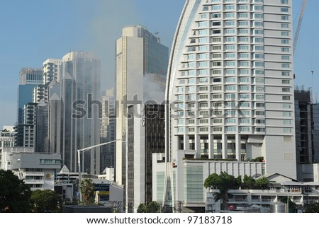 BANGKOK - MAR 5: Smoke rises from Fico Building as firefighters tackle a blaze in the office tower on Mar 5, 2012 in Bangkok, Thailand. The BMA has launched an investigation in the cause of the blaze. - stock photo
