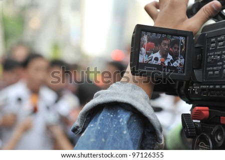 BANGKOK - MAR 5: View through a camera viewfinder as a government official gives an interview to journalists while firefighters tackle a blaze at Fico Building on Mar 5, 2012 in Bangkok, Thailand.