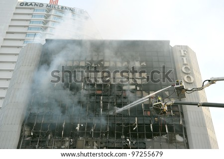 BANGKOK - MARCH 5: Firefighters tackle a blaze at Fico Building on Asoke Road in the city centre on March 5, 2012 in Bangkok, Thailand. The BMA has launched an investigation in the cause of the blaze. - stock photo
