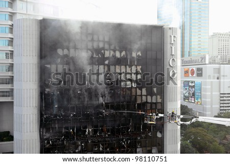 BANGKOK - MARCH 5: Firefighters tackle a blaze at Fico Building on Asoke Road in the city centre on March 5, 2012 in Bangkok, Thailand. The BMA has launched an investigation in the cause of the blaze.