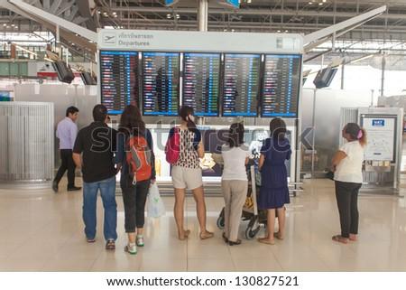 BANGKOK - MARCH 14. Passengers looking at departure display at Bangkok airport on March 14, 2012. Suvarnabhumi airport is world's 4th largest single-building airport terminal. - stock photo