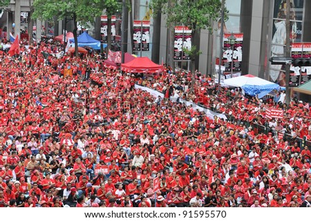 BANGKOK - MAY 19: An estimated 30,000 red-shirt protesters gather at Ratchaprasong Junction to remember those killed in political violence in the previous year on May 19, 2011 in Bangkok, Thailand. - stock photo