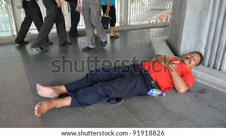 BANGKOK - MAY 19: An unidentified protester sleeps in the street during a large red-shirt rally on May 19, 2011 in Bangkok, Thailand. The rally marked a year since 91 people died in protests.