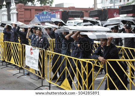 BANGKOK - MAY 31: Policemen stand guard at a barricade during an anti-government People's Alliance for Democracy, or yellow-shirt, rally outside Parliament on May 31, 2012 in Bangkok, Thailand. - stock photo