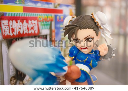 BANGKOK - MAY 7, 2016 : Portrait of Chun-Li mascot to promote the game in Thailand Toy Expo 2016. She is a character from Street Fighter Game, abstract pixel background - stock photo