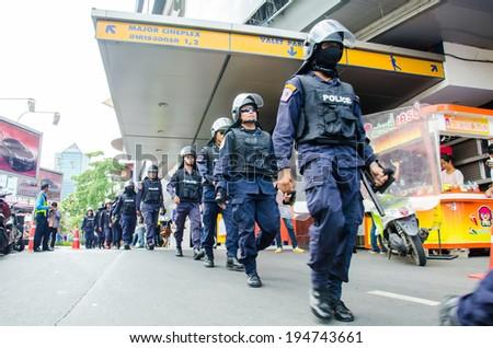 BANGKOK - MAY 24: Riot police stand guard on Major Cineplex Ratchayothin Bangkok during a violent anti-Military coup on May 24, 2014 in Bangkok, Thailand. - stock photo