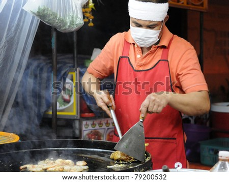 BANGKOK - MAY 30: Unidentified street vendor cooks at a roadside restaurant May 30, 2011 in Bangkok, Thailand. There are more than 16,000 registered street vendors in Bangkok. - stock photo