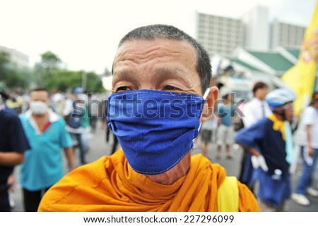 BANGKOK - NOV 24: A masked Buddhist monk attends an anti-government rally organised by the nationalist Pitak Siam group on Nov 24, 2012 in Bangkok, Thailand. Police fired teargas during the rally.   - stock photo
