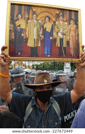 BANGKOK - Nov 24: A masked nationalist protester holds up a portrait of the Thai royal family while attending a city centre anti-government rally on November 24, 2012 in Bangkok, Thailand. - stock photo