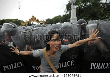 BANGKOK - NOV 24: A protester from the nationalist Pitak Siam movement confronts riot police during a violent anti-government rally on Nov 24, 2012 in Bangkok, Thailand. - stock photo