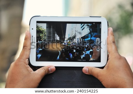 BANGKOK - NOV 4: A protester uses a tablet device to capture an anti-government rally in the Thai capital's central business district on Nov 4, 2013 in Bangkok, Thailand. - stock photo