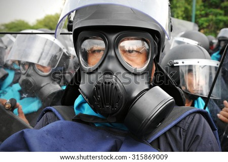 BANGKOK - NOV 24: A riot police officer wears a gas mask during a city centre anti government rally on Nov 24, 2012 in Bangkok, Thailand. Police fired tear gas to deter protesters. - stock photo
