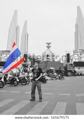 BANGKOK - NOV 30, 2013: an unidentified man standing  in front of Monument Of Democracy during anti-government rally in Bangkok - intensifying a demonstration aimed at toppling the prime minister. - stock photo